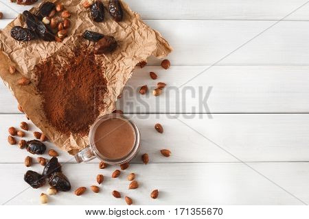 Detox cleanse drink background. Chocolate smoothie ingredients. Natural healthy juice in glass jar for diet or fasting day. Cocoa powder, nuts, date fruit mix on white wood, top view with copy space