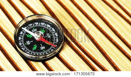 Plastic compass for travel on a wooden background object