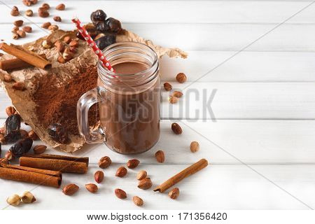 Detox cleanse drink, chocolate smoothie ingredients. Natural healthy nutrition in glass jar for weight loss diet or fasting day. Cocoa powder, nuts, date fruit mix on white wood with copy space