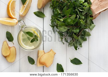 Detox cleanse drink, natural lemonade ingredients. Organic healthy juice in glass jar for weight loss diet or fasting day. Mint, lemon and ginger mix on white wood, top view