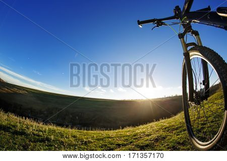 Black mountain bicycle on green grass with blue sky background. Landscape with horizon and green field. Detail of the bicycle. Helm and wheel. Fisheye.