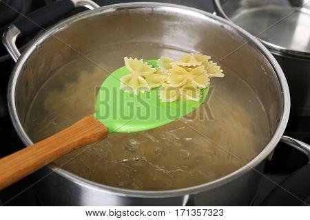 Cooking pasta in pan on stove closeup