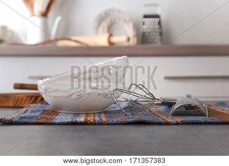 Cooking utensils and plates on kitchen table