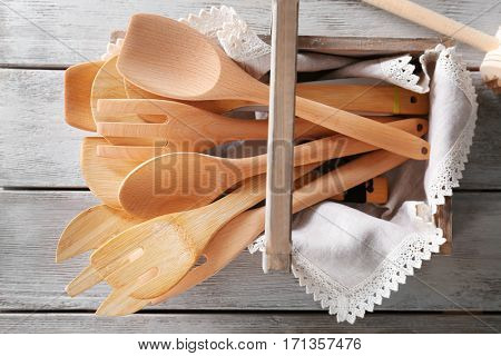 Box with kitchen utensils on wooden table