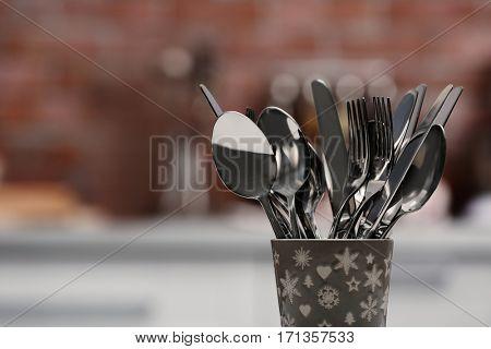 Set of metal kitchen utensils in ceramic cup, closeup