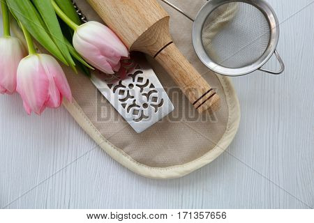 Kitchen utensils and flowers on wooden table