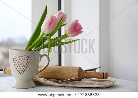 Kitchen utensils and flowers on windowsill