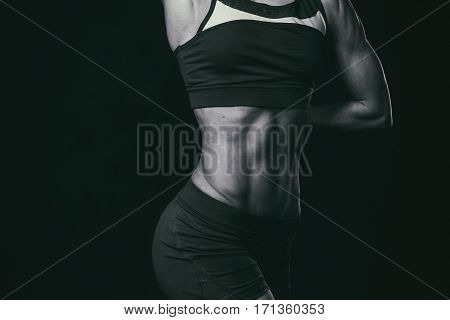 Torso of a young fit woman on a black and white photo.