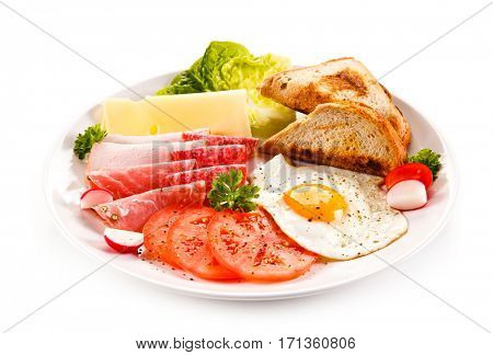 Breakfast - toasts, fried egg and sausages, cheese, ham and vegetables