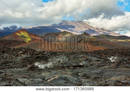 Lava field at the Tolbachik volcano, after eruption in 2012 on background Plosky Tolbachik volcano, Klyuchevskaya Group of Volcanoes
