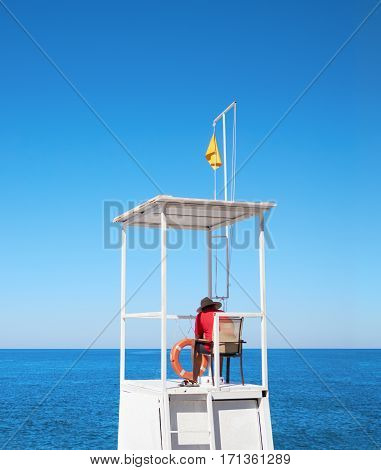 Lifeguard on tower on the background of sky and sea
