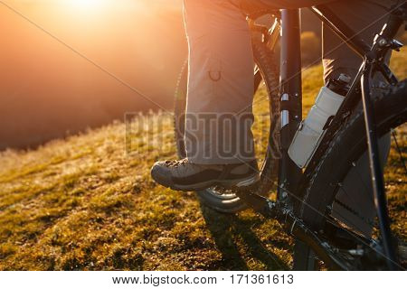 Closeup of cyclist man legs riding mountain bike on outdoor trail in nature. Beautiful landscape. Field with green grass. Spring season. Sunset. Detail of bicycle. Wheel.