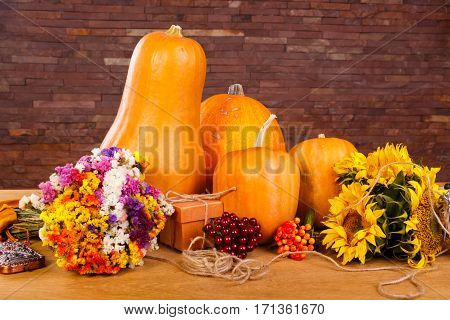 Autumn pumpkins with flowers on wooden board. Haloween