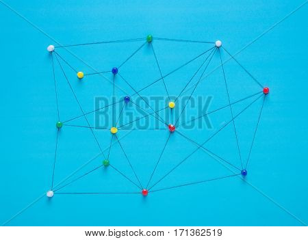 Small network of pins (Thumbtack)and string An arrangement of colourful pins linked together with string on a pale background suggesting a network of connections.