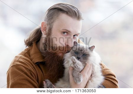 Young bearded man holding fluffy cat on blurred background