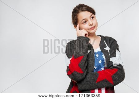 Pensive young girl in clothes in the form of American flag looking away and holding finger near the head