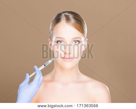 Young and beautiful woman having skin injections over brown background. Plastic surgery concept.