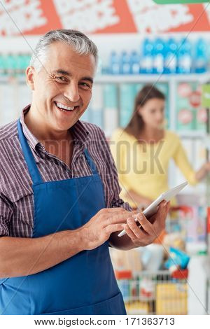 Supermarket Clerk Using A Tablet