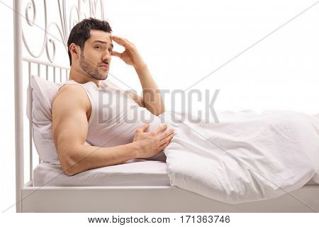 Worried guy lying in bed isolated on white background
