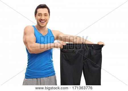 Happy man holding a pair of oversized pants isolated on white background