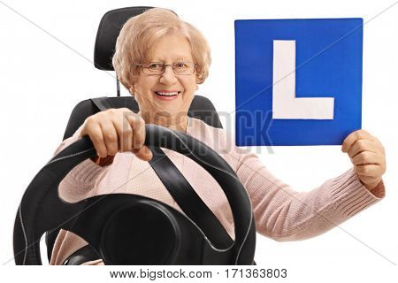 Happy mature woman sitting in a car seat and holding an L-sign isolated on white background