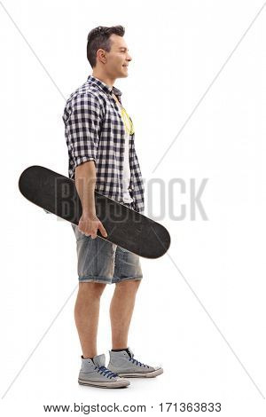 Full length profile shot of a skater holding a skateboard and waiting in line isolated on white background