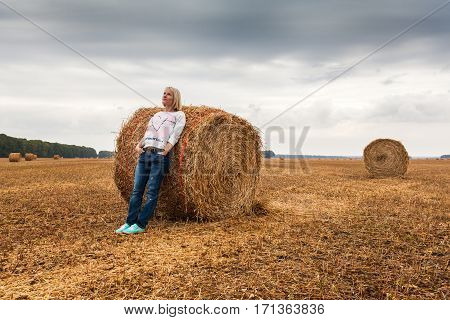 A young woman stands on the field, leaning on a sheaf of hay against the background of dark dramatic sky with clouds
