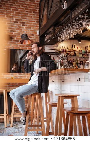 Vertical image of bearded man sitting on bar and talking on phone