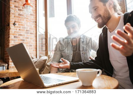 Side view of Surprised Smiling Friends sitting by the table with laptop in cafe