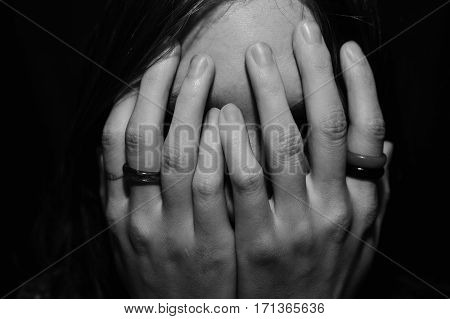 Woman covering face with hands close up
