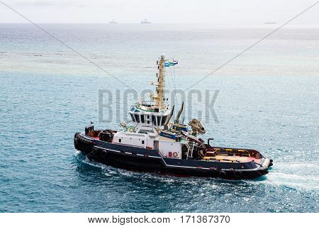 A large tugboat sailing through blue water off Aruba