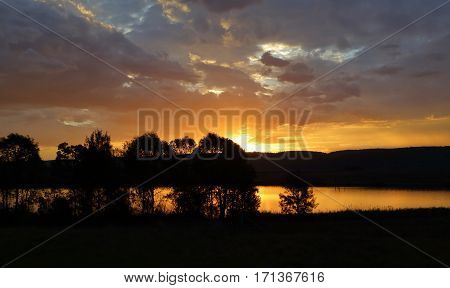 Beautiful clouds at sunset colour the sky and reflect in the lakes at Penrith with silhouetted trees and shrubsAustralia