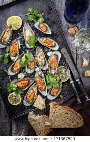 Backed Green Shell Mussels on an old rustic sheet with White Wine and Bread