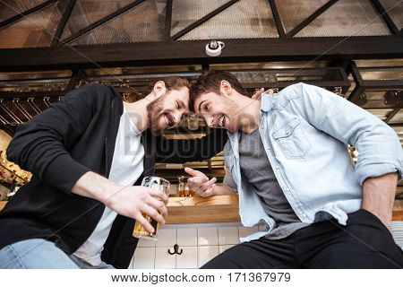 View from below of Drunk friends sitting on bar in cafe with cups of beer