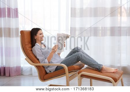 Young woman sitting on modern deck chair and reading newspaper in light room