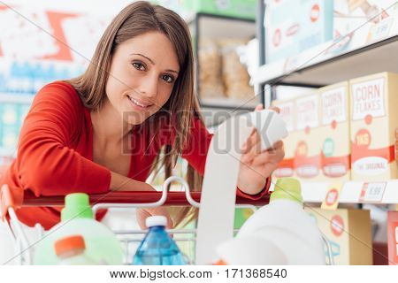 Smiling woman doing grocery shopping at the supermarket and checking a long receipt she is leaning on the full cart