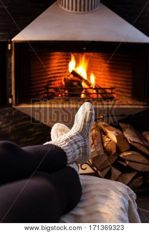 Christmas and winter mood. Woman sitting at a cosy fire warming her cold feet.