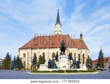 Unirii square and the medieval gothic st michael church in cluj napoca romania, statue of matei corvin