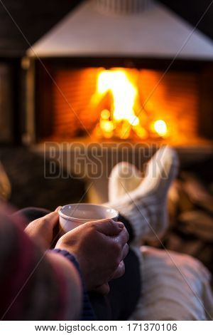 Woman sitting at a cosy fire warming her cold feet.