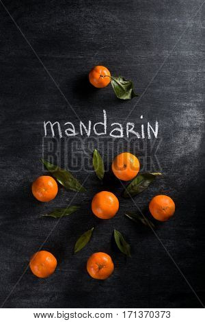 Top view photo of mandarines over dark chalkboard background
