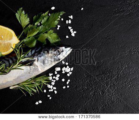 Mackerel on a black background, herbs and lemon