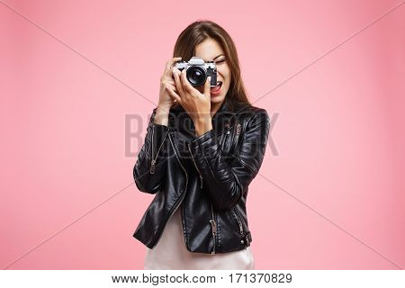 Stylish young woman in trendy black leather jacket holding old camera, taking pictures, looking glad