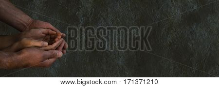 Dark and desperate times - wide dark rough stone grunge background with a man's hands cradling a woman's hands cupped in begging gesture with dark lighting and plenty of copy space