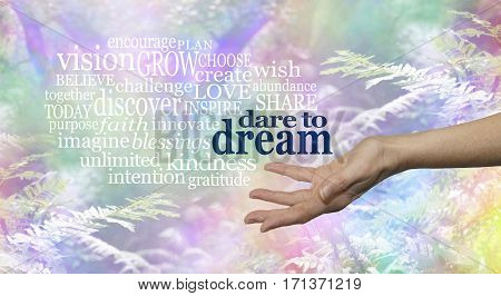 Dare to Dream word cloud - Female hand outstretched palm up on a rainbow woodland background and the words DARE TO DREAM floating above surrounded by a relevant word cloud