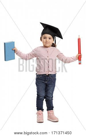 Full length portrait of a little girl with a mortarboard holding a book and a pencil isolated on white background