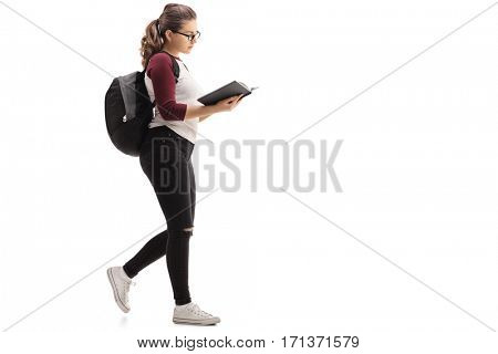 Full length profile shot of a female student with a backpack walking and reading a book isolated on white background