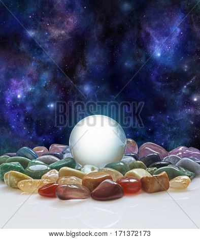 Crystal ball, healing crystals and the Universe - large clear crystal ball with a selection of chakra colored healing crystals with a background of the night sky deep space