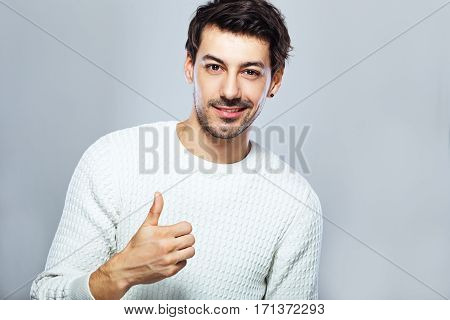 half length portrait of young joyful man showing thumbs up wearing white pullover standing next to color background