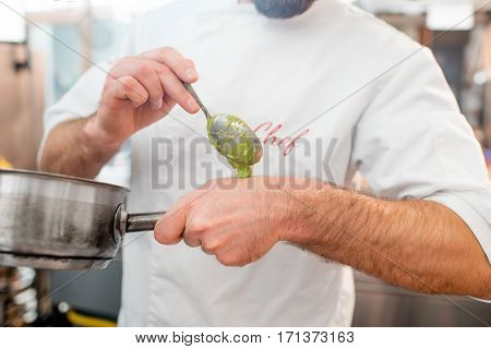 Chef cook putting sause on the hand for tasting