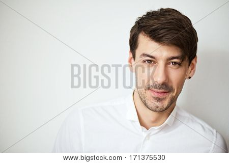 portrait with grinning handsome man in white shirt looking at camera posing next to color background